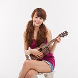 Young Asian woman playing ukulele. Royalty Free Stock Images