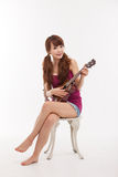 Young Asian woman playing ukulele. Stock Photography