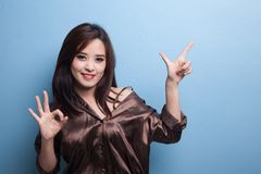 Young Asian woman point and show OK. Royalty Free Stock Photo