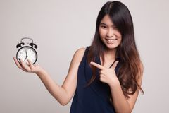Young Asian woman point to a clock. Stock Photo