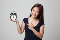 Young Asian woman point to a clock. Royalty Free Stock Image