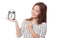 Young Asian woman point to a clock. Royalty Free Stock Photography