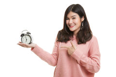 Young Asian woman point to a clock. Royalty Free Stock Photos