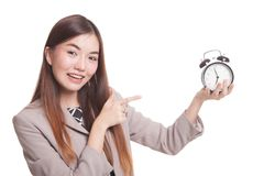 Young Asian woman point to a clock. Royalty Free Stock Images
