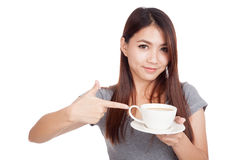 Young Asian woman point to cup of coffee. Isolated on white background stock photo