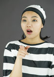 Young Asian woman pointing and looking shocked in prisoners uniform Stock Photos