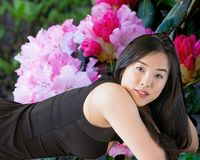 Young Asian woman poses against a backdrop of rhododendron flowers. Smiling young woman with dark black hair in a portrait composition showing her in a black stock images