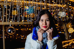 Young Asian woman posing against the backdrop of a Christmas tree with garlands to night. Stock Photography