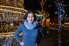 Young Asian woman posing against the backdrop of a Christmas tree with garlands to night. Royalty Free Stock Image