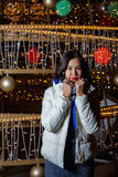 Young Asian woman posing against the backdrop of a Christmas tree with garlands to night. Stock Images