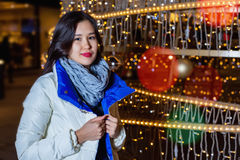 Young Asian woman posing against the backdrop of a Christmas tree with garlands to night. Royalty Free Stock Photos