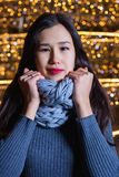 Young Asian woman posing against the backdrop of a Christmas tree with garlands to night. Royalty Free Stock Photo