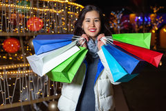 Young Asian woman posing against the backdrop of a Christmas tree with garlands to night Stock Photos