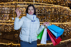 Young Asian woman posing against the backdrop of a Christmas tree with garlands to night Stock Image