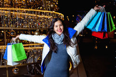 Young Asian woman posing against the backdrop of a Christmas tree with garlands to night Stock Images