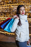Young Asian woman posing against the backdrop of a Christmas tree with garlands to night. After shopping Stock Photography