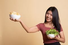 Young Asian woman with potato chips and salad. On beige background royalty free stock image