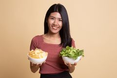 Young Asian woman with potato chips and salad. On beige background stock photo