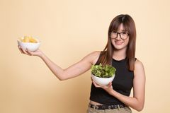 Young Asian woman with potato chips and salad. On beige background royalty free stock photos