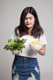 Young Asian woman with potato chips and salad. Royalty Free Stock Photos
