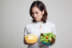 Young Asian woman with potato chips and salad. Royalty Free Stock Photography