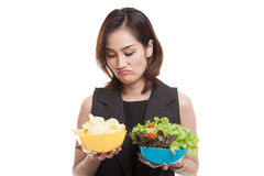Young Asian woman with potato chips and salad. stock photo