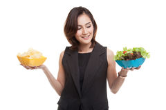 Young Asian woman with potato chips and salad. Young Asian woman with potato chips and salad isolated on white background stock photos