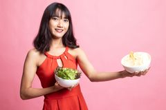 Young Asian woman with potato chips and salad. On pink background royalty free stock photos