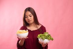 Young Asian woman with potato chips and salad. On pink background stock image
