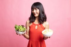 Young Asian woman with potato chips and salad. On pink background stock photo