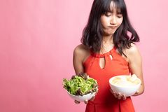 Young Asian woman with potato chips and salad. On pink background royalty free stock photography