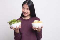 Young Asian woman with potato chips and salad. On white background royalty free stock images
