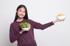 Young Asian woman with potato chips and salad. On white background royalty free stock photo