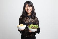 Young Asian woman with potato chips and salad. On white background royalty free stock photos