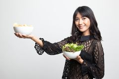 Young Asian woman with potato chips and salad. On white background royalty free stock image
