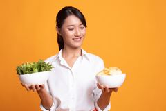 Young Asian woman with potato chips and salad. On yellow background royalty free stock photography