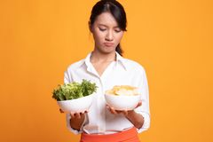 Young Asian woman with potato chips and salad. On yellow background stock image