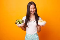 Young Asian woman with potato chips and salad. Young Asian woman with potato chips and salad on bright yellow background royalty free stock image