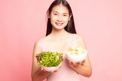 Young Asian woman with potato chips and salad. On pink background stock photography