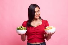 Young Asian woman with potato chips and salad. On pink background stock images
