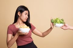 Young Asian woman with potato chips say no to salad. On beige background stock image