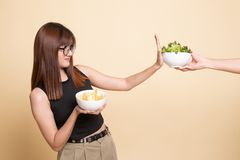 Young Asian woman with potato chips say no to salad. On beige background royalty free stock photo