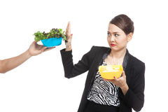 Young Asian woman with potato chips say no to salad Royalty Free Stock Photos