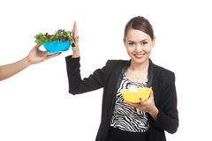 Young Asian woman with potato chips say no to salad Stock Photo