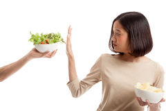 Young Asian woman with potato chips say no to salad Royalty Free Stock Image