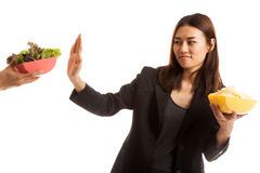 Young Asian woman with potato chips say no to salad. Stock Image