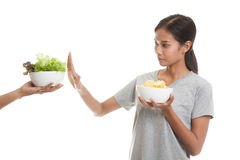 Young Asian woman with potato chips say no to salad. Royalty Free Stock Photo