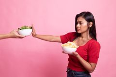 Young Asian woman with potato chips say no to salad. On pink background stock photography
