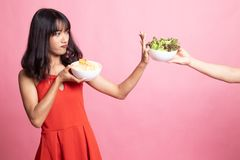 Young Asian woman with potato chips say no to salad. On pink background royalty free stock images
