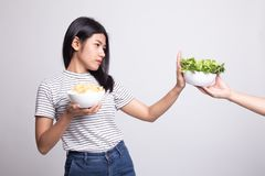 Young Asian woman with potato chips say no to salad. On white background royalty free stock images
